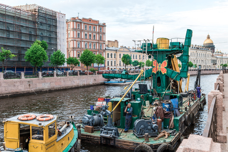 lifeboat station: St.Petersburg, Russia - May 16, 2016: Boat maintenance station on Moyka river. The workers are smoke-breaking.