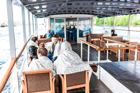 excursion: St.Petersburg, Russia - May 17, 2016: Excursion on Neva river. Passengers on the top deck of restaurant ship in windy summer day.