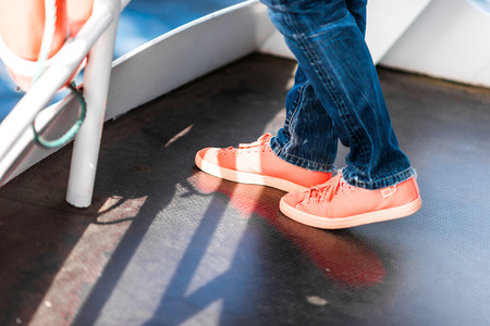 ship deck: Feet on ship deck wearing dark blue jeans and orange sneakers. Stock Photo