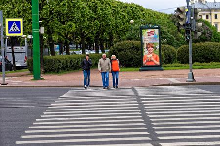 passerby: St.Petersburg, Russia - June 10, 2016: Men and woman on pedestrian zebra crossing near Letniy garden.