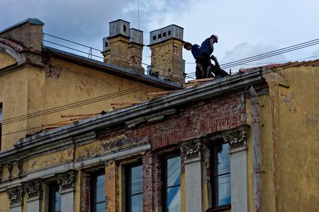 housetop: St.Petersburg, Russia - June 10, 2016: Workers on the roof repairing the housetop.