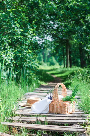 footway: Rectangle basket with green vegetables, forks and knives standing on the plank footway among the grass. Stock Photo