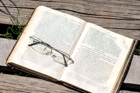 footway: Summer midday. Book and eyeglasses on the plank footway. Stock Photo