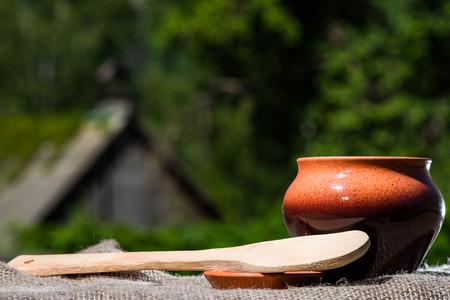 kasha: Little ceramic jar and big wooden spoon on burlap over foliage background. Stock Photo