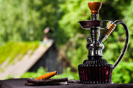 purge: Deep purple glass hookah on the open air simmer background. Stock Photo