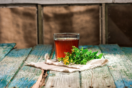 wort: Glass of tea and St.John wort herb on the shabby wooden plank table. Stock Photo