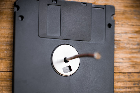 clavados: Obsolete discette fixed on the wooden wall by nail. Concept of wrong data storage.