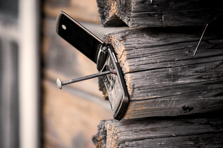 nonsense: Old cell phone fixed on the wooden wall by nail. Concept of barbarity, consumerism or uncontrolled progress.