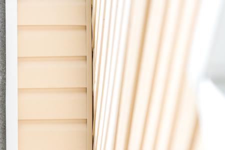soffit cladding: House roof soffit in beige siding and white fittings.