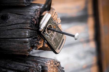 fixed: viejo teléfono celular fijo en la pared de madera por el clavo. Concepto de la barbarie, el consumismo o el progreso incontrolado.