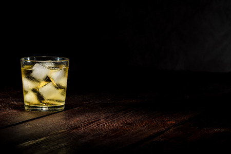 cordial: Drinking glass with ice cubes and yellow liquid on the dark wooden surface.
