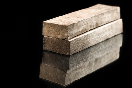 lumbering: Cut timber bars for construction isolated on black background