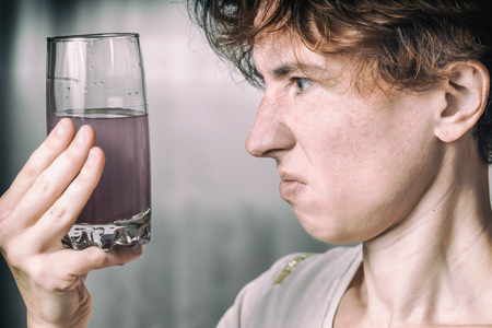ordinary woman: Ordinary woman looks at an unknown liquid in the glass. Color split toning. Stock Photo