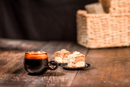awaking: Closeup of wooden table set with cup of coffee, nut caces and accessories on black background. Selective focus Stock Photo