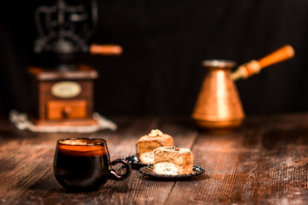 brisk: Closeup of wooden table set with cup of coffee, nut caces and accessories on black background. Selective focus Stock Photo