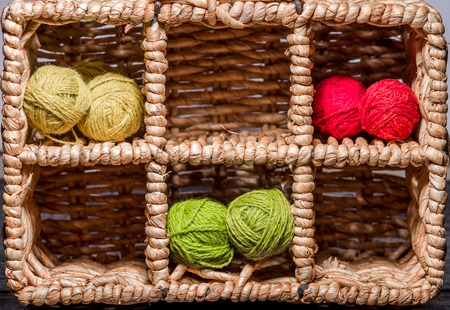 gomitoli di lana: Many small balls of wool of rainbowcolors in wicker cells.