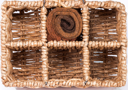 garments: Rolled garments in warm colors in square cells of wicker storage