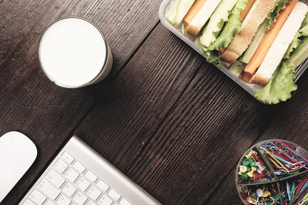dining out: Lunch box with sandwich bread and fresh vegetables and glass of  alternative milk beverage on dark wood background. Concept of healthy dining out.