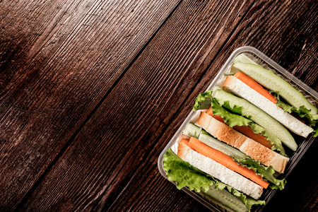 dining out: Lunch box with sandwich bread and fresh vegetables on dark wood background. Concept of healthy dining out.