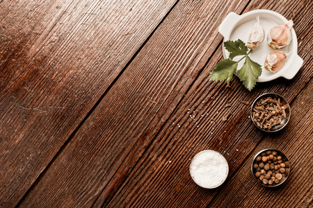 celeriac: Salt, pepper and other spices on the right part in dark wooden table. Flat lay