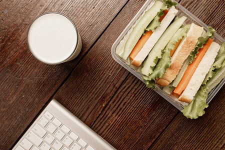 out to lunch: Lunch box with sandwich bread and fresh vegetables and glass of  alternative milk beverage on dark wood background. Concept of healthy dining out.