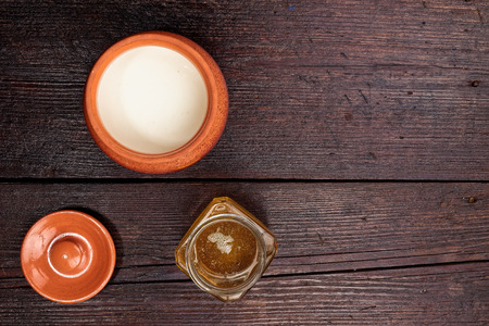 fortify: Pot of milk and jar of honey  on the dark wooden surface. Flat lay.