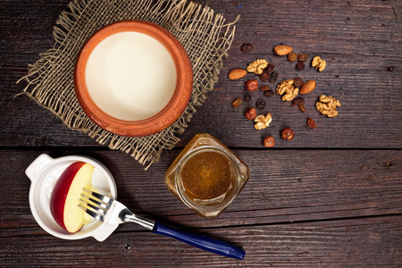 apple and honey: Pot of milk, apple, honey, corn flakes and nuts on the dark wooden surface. Flat lay.