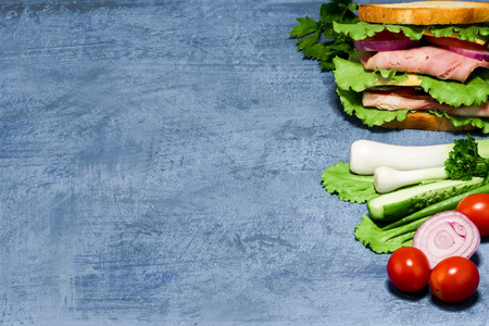potherb: Double sandwich of bread, ham, cheese, tomato, cucumber, onion and lettuce and its ingredients on spotty blue background. Stock Photo