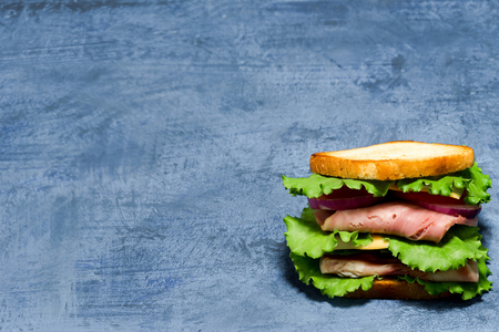 potherb: Double sandwich of bread, ham, cheese, tomato, cucumber, onion and lettuce on spotty blue background.