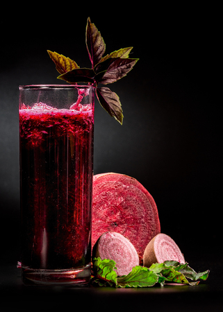 pulpy: Fresh pulpy juice or smoothie of beet and basil over black background.