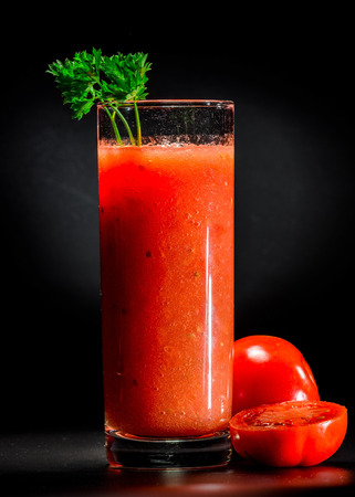 pulpy: Fresh pulpy juice or smoothie of red tomato over black background. Stock Photo