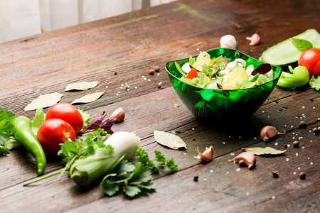 potherbs: Fresh vegetables: tomatoes, cucumber, pepper, leek, salad, potherbs, spices and salad bowl on the dark wood table