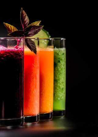 pulpy: Fresh pulpy juices or smoothies of beet, tomato, carrot and cucumber over black background.