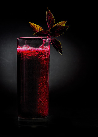 pulpy: Fresh pulpy juice or smoothie of beet and basil over black background. Concept of healthy eating