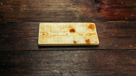 venge: Cutting board of light wood on the table of dark wood