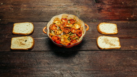 cocozelle: Pan with baked ratatouille - traditional French vegetarian dish - and toasts on the table Stock Photo