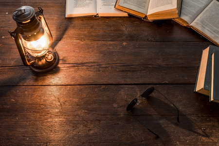 glasswear: Old-fashioned kerosene lamp and opened books on the dark table in twilight. Soft focus Stock Photo