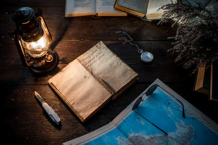 glasswear: Old-fashioned kerosene lamp, map and accessories on the dark table in twilight.Soft focus