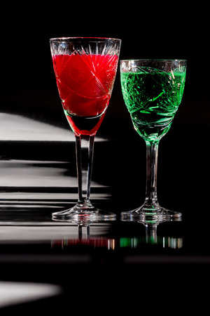 cutglass: Wineglasses of cut-glass full of colorful liquids over black reflective background