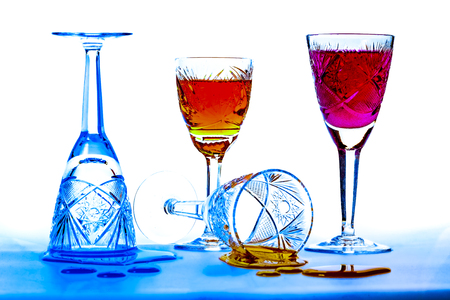 cutglass: Wineglasses of cut-glass full of colorful liquids over white and blue background Stock Photo