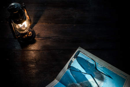 glasswear: Old-fashioned kerosene lamp, map and accessories on the dark table in twilight. Soft focus