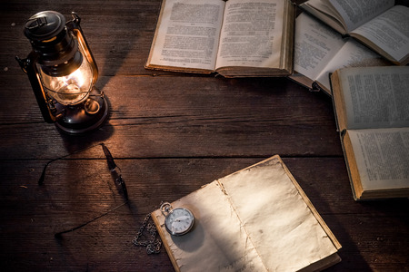 glasswear: Old-fashioned kerosene lamp and copybook on the dark table in twilight. Soft focus Stock Photo