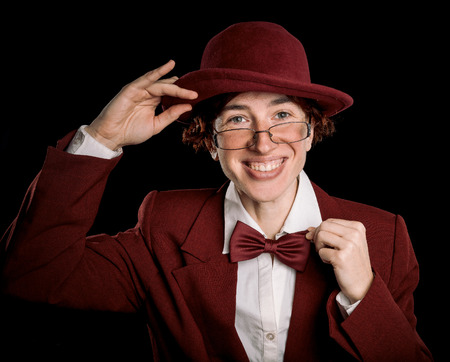 exaggerated: Strange person wearing red suit and bowler taking off the hat and straightening the bow tie.