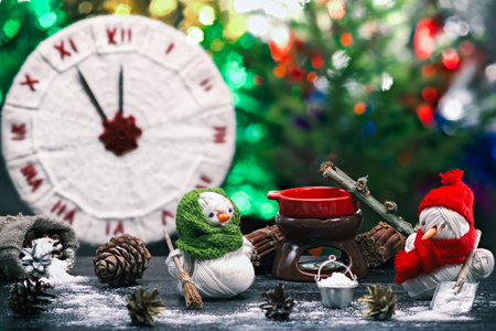brooming: Handmade toy snowman and snowgirl of yarn skeins brooming and shoveling the snow over background of knitted clock and shiny Christmas decorations. Color toning