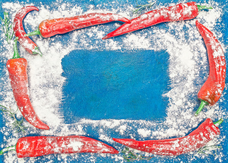 potherb: Frame of red chile pepper and potherb branches under the flour over blue background. Flat lay. Color toning Stock Photo