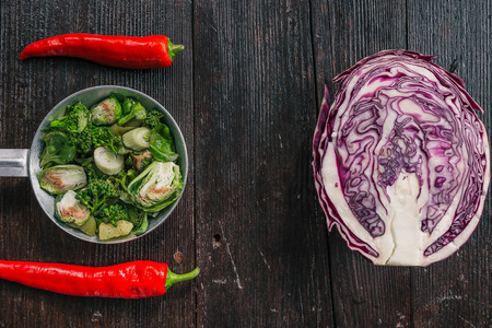 brussel: Red cabbage, broccoli, brussel sprouts and chili peppers on the dark wooden surface