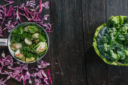 broccoli sprouts: Green and red cabbage, broccoli and brussel sprouts, fresh and cooked on the dark wooden surface Stock Photo