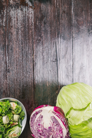 wooden surface: Green and red cabbage, broccoli and brussel sprouts, fresh and cooked on the dark wooden surface Stock Photo