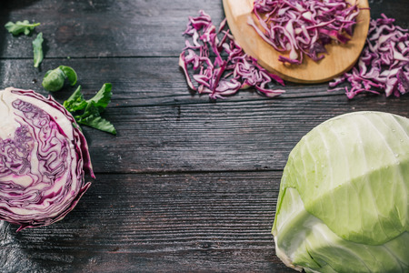 brussel: Green and red cabbage, broccoli and brussel sprouts, fresh and cooked on the dark wooden surface Stock Photo