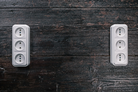 grounded plug: White triple electric sockets on the dark wooden surface